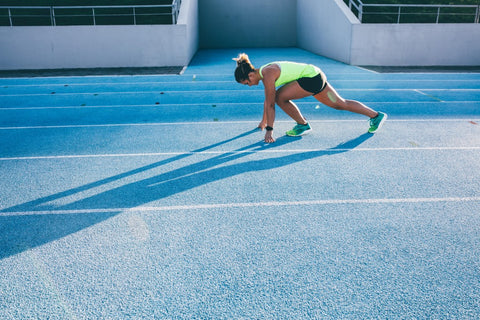 Woman in starting position on blue track