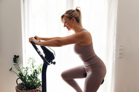 Side view of woman riding stationary bike