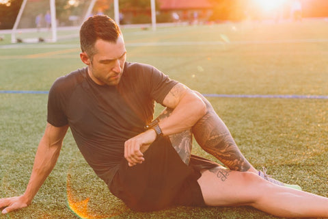 Man on turf stretching looking at watch