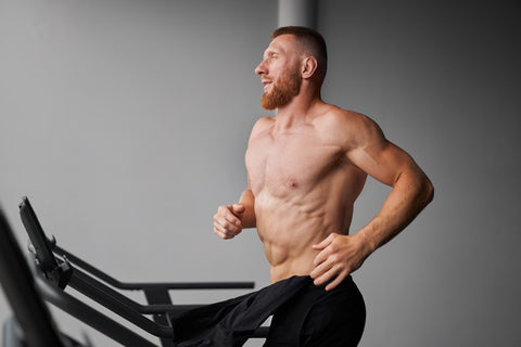 Strong man running on treadmill without shirt on