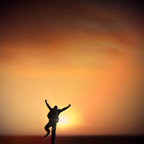 Sky with sun setting and person jumping in front of sun