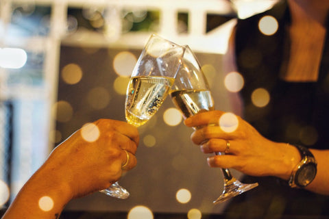 Two people tapping champagne glasses