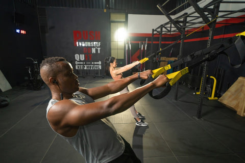Man pulling himself up with TRX straps while working out