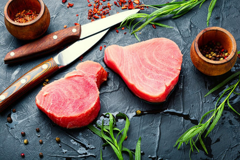 Tuna steaks on cutting board next to knives and greens