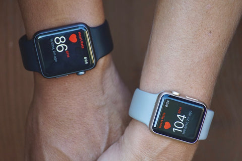Man and woman with apple watches displaying their heartrate