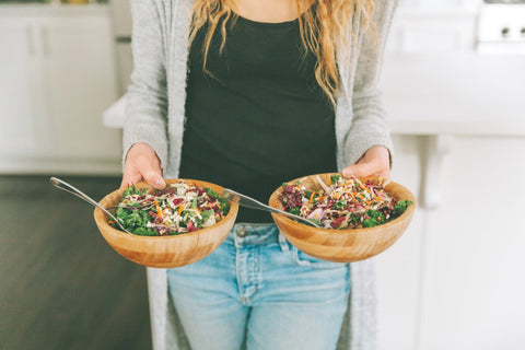 Woman standing holding two wooden bowls full of salad