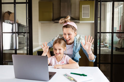 Mother and daughter on waving at laptop while video chatting