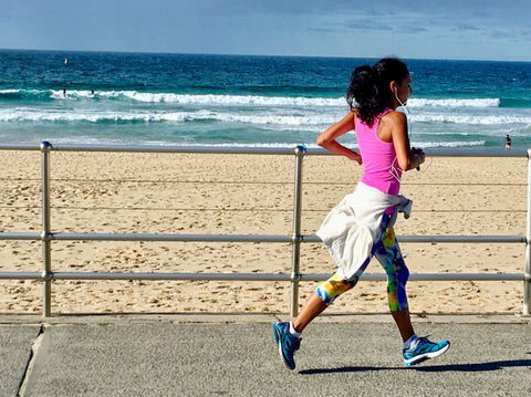 Woman running on the beach for vitamin D.