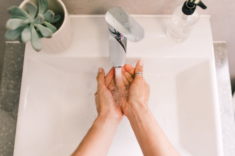 Above view of hands being washed at bathroom sink