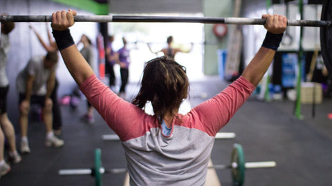 Woman lifting weights in a gym.