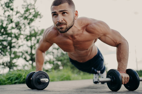 Man building lean muscle doing pushups with weights in both hands