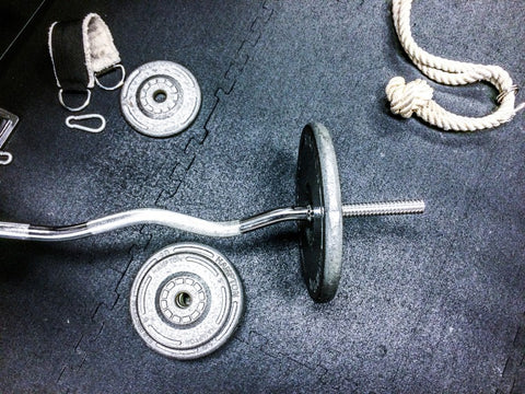 Barbell with weight and plate weights on gym ground