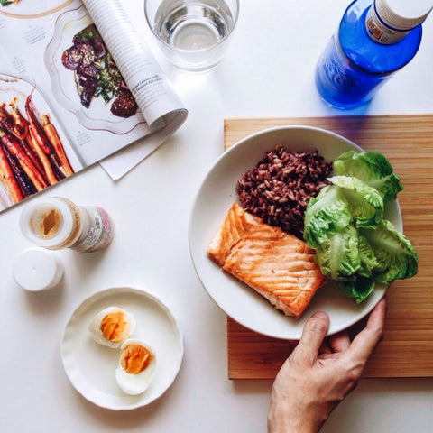 Salmon, bean, and leaf meal on plate on cutting board next to cook book