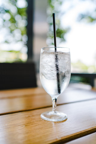 Wine glass full of water on table with black straw