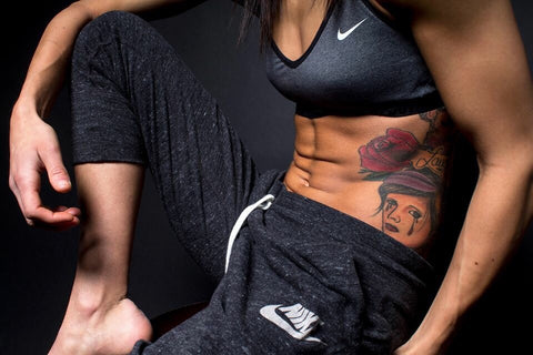 Woman bent over with abs and arms on leg