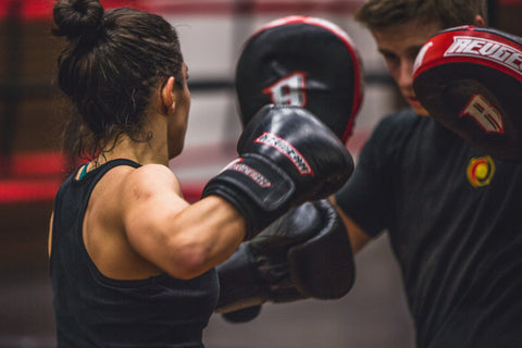 Woman with boxing gloves on hitting mans mits