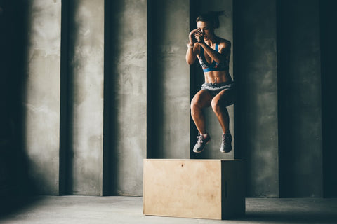 Woman doing box jumps in gym