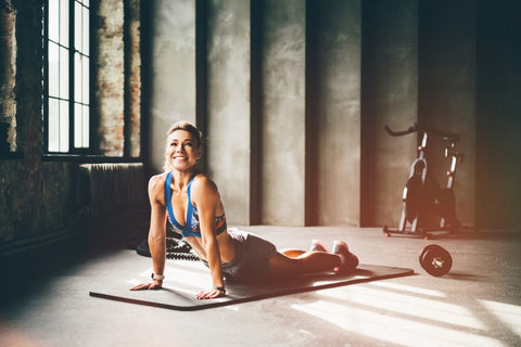 Woman smiling while doing cobra position on yoga mat