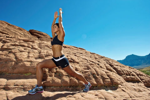 Woman doing lunges in front of canyon