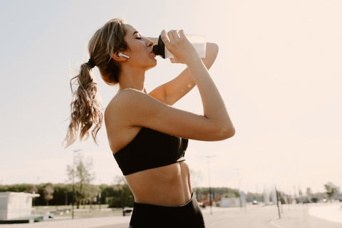 Woman leaning head back while drinking protein shake