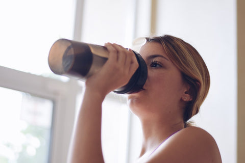 Woman drinking out of black shake bottle