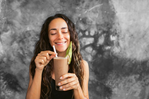 Woman smiling while holding the straw of her chocolate protein shake