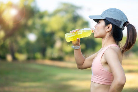 Side view of woman in sports bra with hat drinking yellow beverage