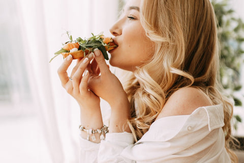 Side view woman eating bread with salmon and greens on top