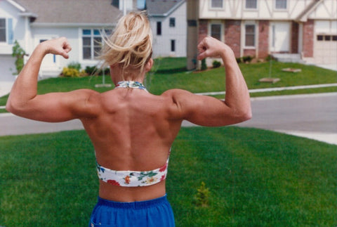 Back view of woman flexing in front yard