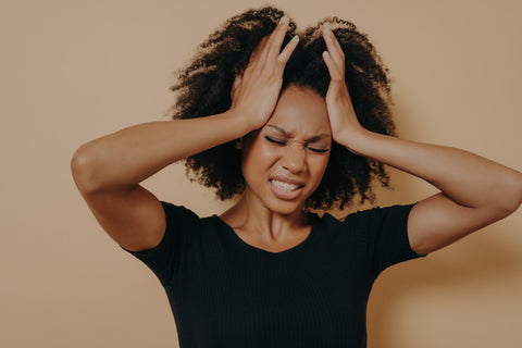 Woman running hands through hair and holding head due to head ache