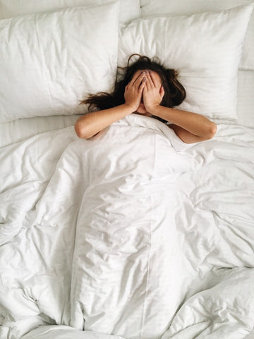 Woman with hands over face in bed under covers