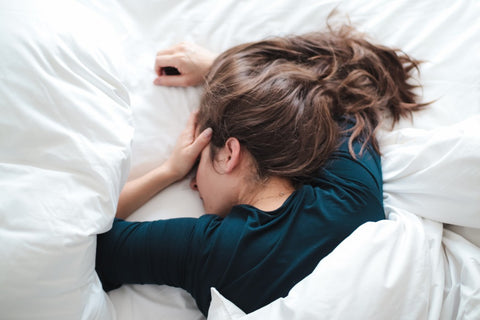 Woman in bed under covers with hand on head