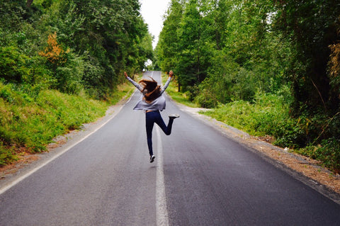 Happy woman jumping in middle of street surrounded by woods
