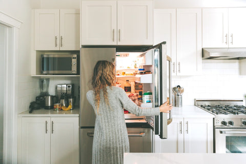 Hungry woman opening stainless steal kitchen fridge