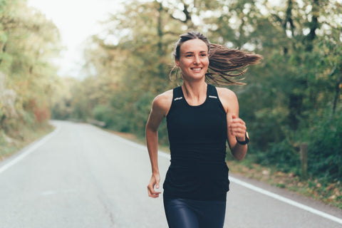 Woman smiling while running on path in woods