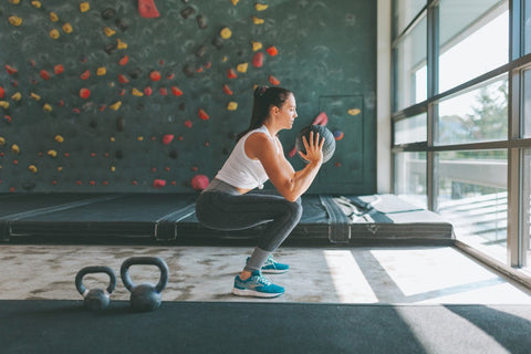 Woman squatting with a medicine ball in gym