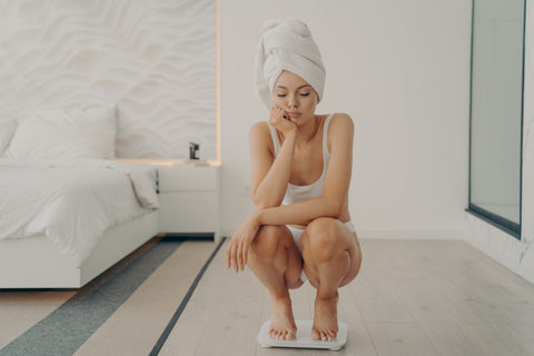 Sad woman squatting on scale with shower towel on head