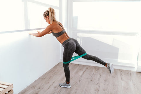 Woman using wall as support while she uses resistance bands on legs