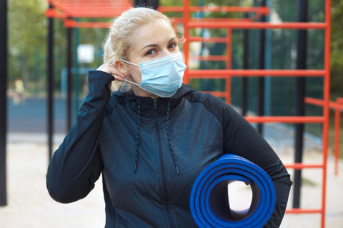 Woman putting mask on while holding yoga mat under arm