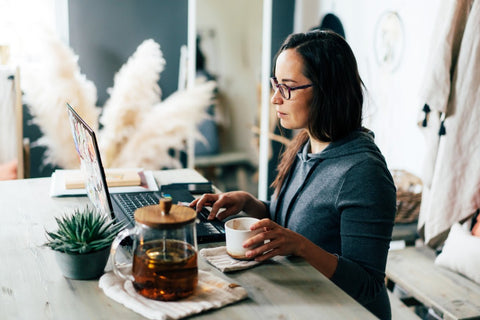 Woman staring at laptop on desk with coffee cup next to her