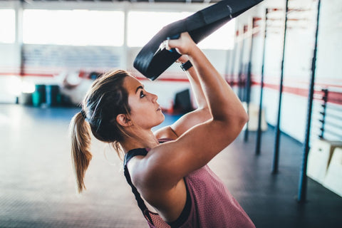 Woman pulling herself up with workout straps in gym