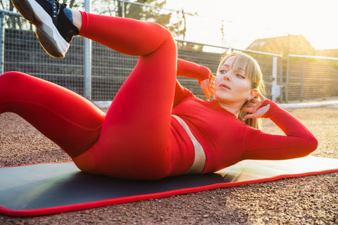 Woman wearing all red outfit doing bicycle crunches on yoga mat