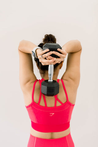Back view of woman lifting dumbbell with both arms