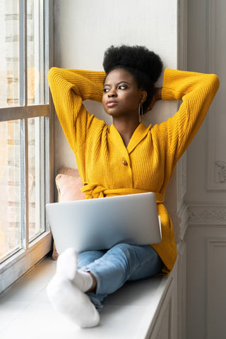 Woman with arms above head and laptop on legs sitting on window sill