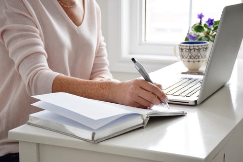 Woman at desk writing on notepad next to laptop