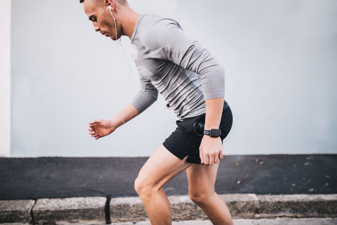 Man in running stance getting ready to run with watch on