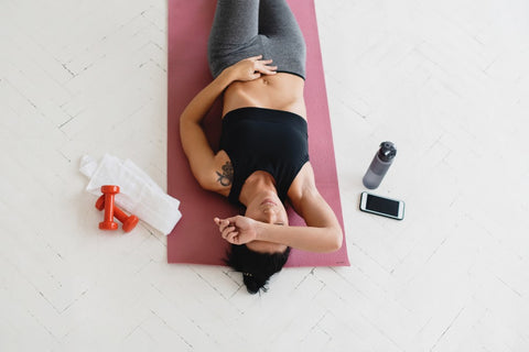 Woman resting on back on yoga mat during home workout