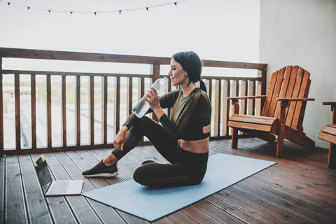 Woman drinking water while working out on yoga mat