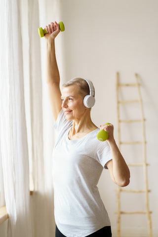 Older woman lifting dumbells over head with headphones on