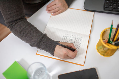 Writing down workout in book on desk